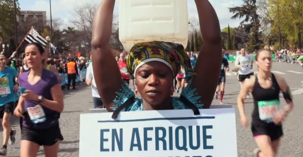 Paris Maratonu'nu Su Kovası Taşıyarak Yürüyen Bir Kadın